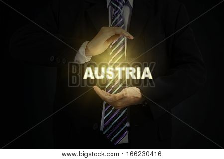Picture of young businessman wearing formal suit and protecting a Austria word