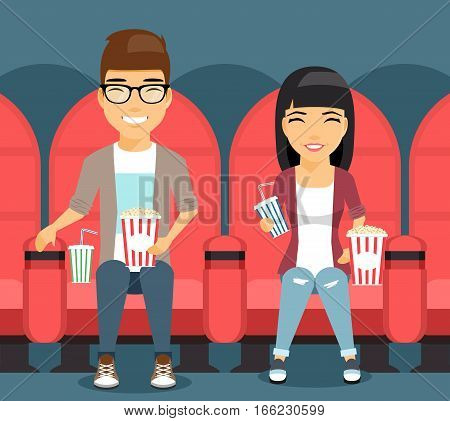 Young couple man and woman in a movie theater laugh on the film. The guy in the river holding the popcorn. Girl with soda in hand. Happy people.