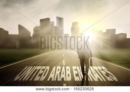 Businessman walking on the street while carrying a briefcase with United Arab Emirates word at sunrise