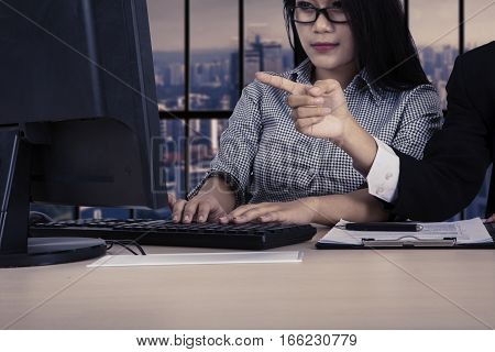 Hand of male manager pointing at the monitor to show the task on his employee in the office