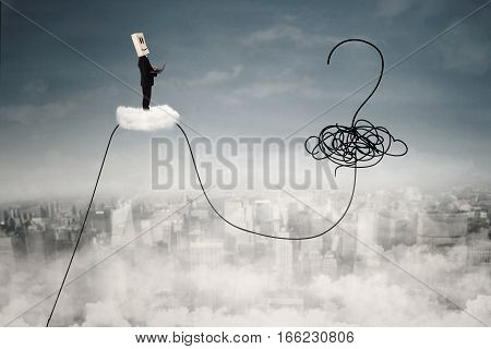 Image of a businessperson with laptop and cardboard head standing on the cloud with question mark at the sky