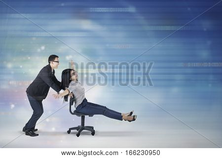 Picture of young businesswoman sitting on the chair in cyberspace while moving fast helped by her partner