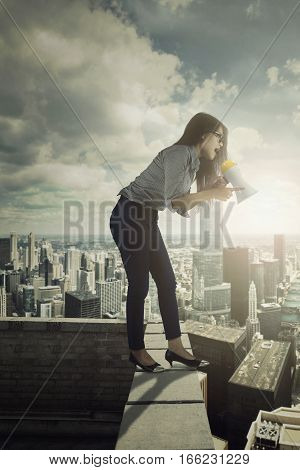 Picture of young angry businesswoman shouting by using a megaphone while standing on the top of building