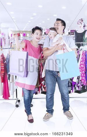 Full length of cheerful family shopping together while pointing something in fashion store