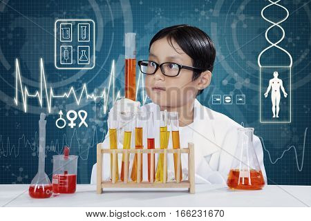 Little boy working in the laboratory and analyze his experiment on the test tube