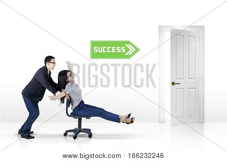 Picture of female entrepreneur sitting on the chair and moving fast helped by her partner toward success door isolated on white background