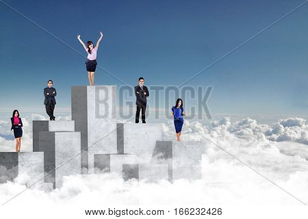 Group of successful entrepreneurs standing on concrete wall with success expression at the sky