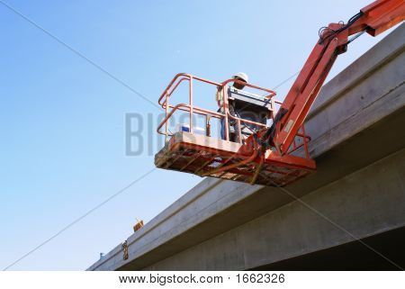Workman inspects new bridge concrete from a man lift poster