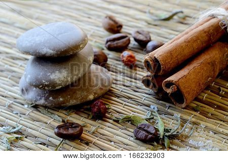 Spa still life - closeup of massage stones,cinnamon,coffee beans,salt,dried hawthorn berries and lavender leaves