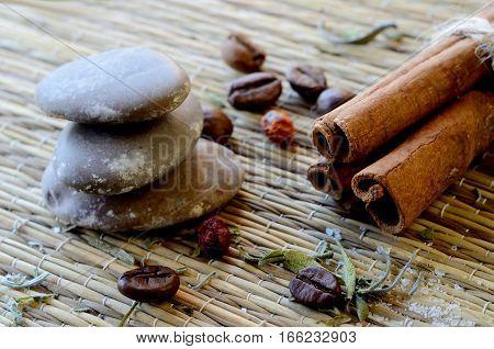 Spa still life - closeup of massage stones,cinnamon,coffee beans,salt,dried hawthorn berries and lavender leaves