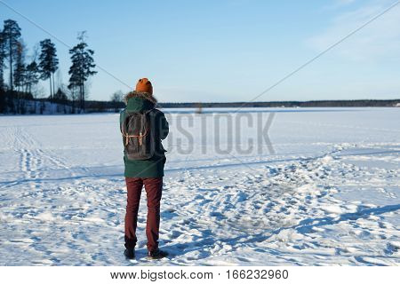 Traveler look to the horizont in winter day. Back view of thinking guy with dreams. Man in green jacket red hat look to snowy field and choose right of two ways.