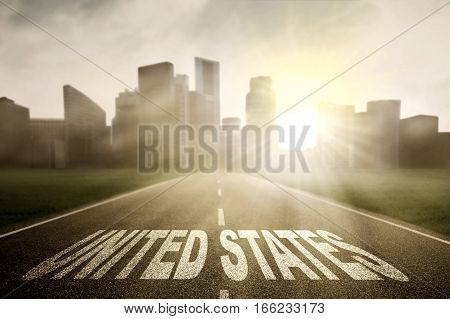 Asphalt highway towards to a town with sunrise and United States word