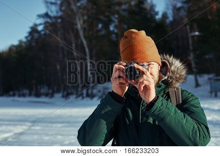 Close up portrait of photographer with vintage camera. Bearded backpacker making photo in sunny day contryside with snowy field and green forest. Travel concept with free space for advertising.