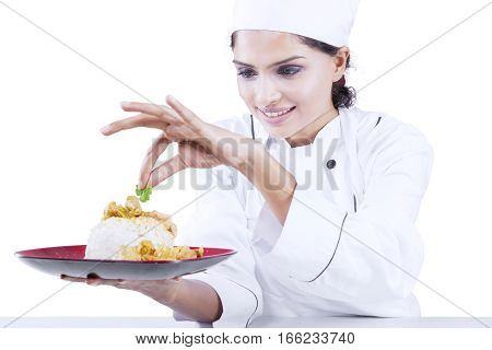 Image of a young Indian chef preparing a dish of yummy food while putting parsley in the studio