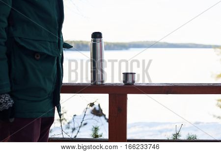 Part of tourist in forest trip. Relax and rest time with pot of hot tea with winter snowy landskape background. Copy space for advertising travel goods or tourism stuff.