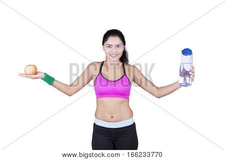 Indian young woman wearing sportswear while holding an apple and a bottle of mineral water in the studio