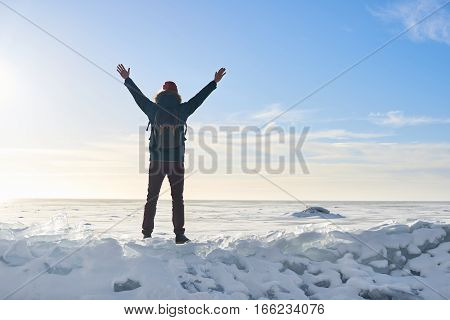 Man on the top. Finish of the way. Ice desert in sunny day. Concept of win. Champion of foot travel. Openning new horizon. Free space for advertising. Victory.