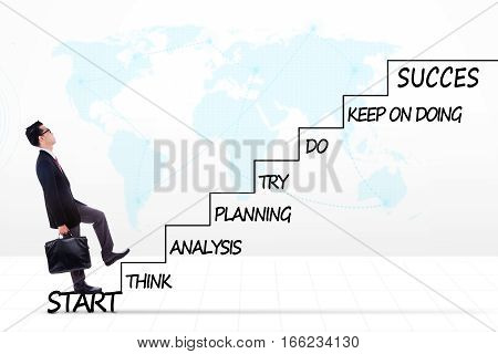 Photo of a young male entrepreneur climbing upward a stairway with strategy plan to success shot with world map background