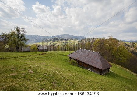 Old lodge on a green meadow on a background of mountains. Carpathians