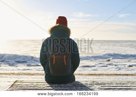 Backpacker sit and look to the sea. Dreaming concept. Frozen winter sea. Open space to the horizont. Freedom feeling. Place for thinking.