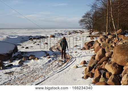 Back view of going man with backpack on the snowy beach to the horizon. Free person walking in sunny winter day. Healthy life countryside.