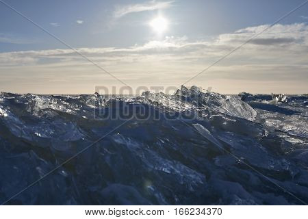 Frozen sea under daily sun in Alaska. Winter day background. Cold weather concept with light blue sky and white clouds.