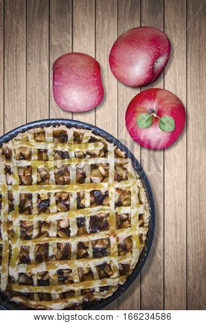 Close up of apple pie and three red apple fruit on the wooden table