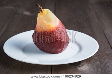 one poached pear on white plate on dark wooden background