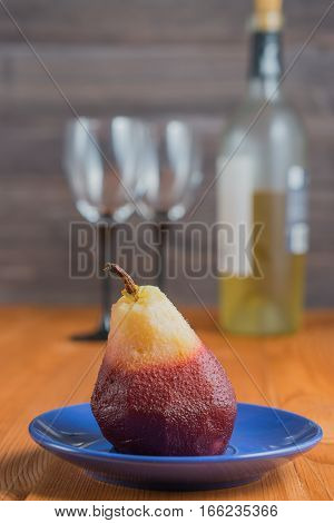 one poached pear on little blue plate. bottle of wine and two wine glasses