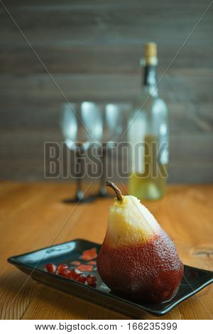 one poached pear on little black rectangle plate. bottle of wine and two wine glasses