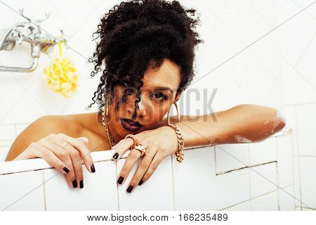 young afro-american teen girl laying in bath with foam, wearing swag jewelry flawless