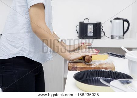 Close up of woman cooking apple pie by using rolling pie while standing in the kitchen