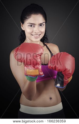 Image of a young Indian woman standing with red boxing gloves on the black background