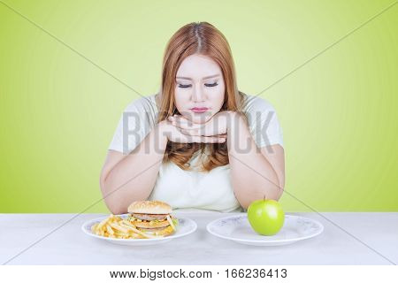 Overweight woman looks confused looking at a fresh apple fruit and hamburger on the table