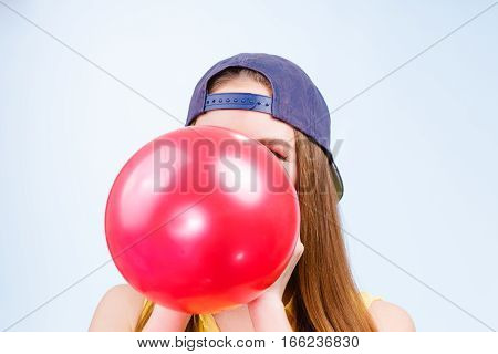 Female Teenager Inflating Red Balloon.