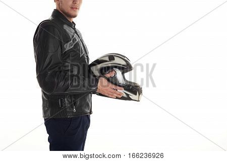 Young man keep black and white motorcycle helmet in front of himself. Boy in leather dark jacket look to the camera. Free space for advertising motor goods or text.