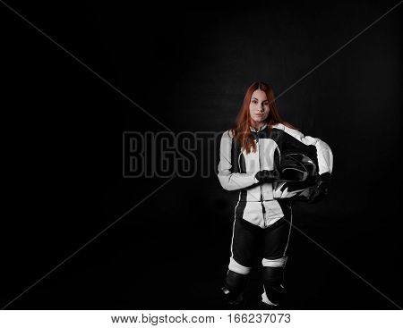 Extreme young girl with red hair in protection body armor of motorcycle sport with helmet in hands. Tired woman after the race on black background with copy space for advertising text.