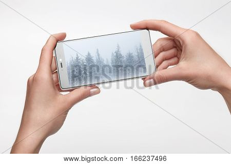 Female hands holding smartphone with picture on screen. Mobile photography concept focus on screen and fingers. Screen isolated with clipping path
