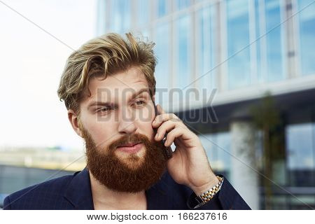 Close up conversation concept. Attractive doubting man talk by mobile phone and walk outdoor near business buildings. Serious person in suit.