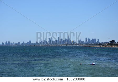 Melbourne skyline from Brighton Beach Gardens (Victoria Australia). View over the city of Melbourne in the Port Phillip Bay and colourful bathing boxes on the beach.