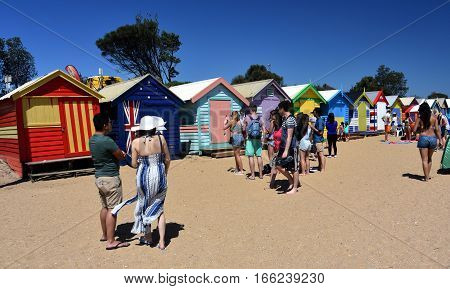 Melbourne Australia - December 30 2016. People taking photos at the bathing boxes. Brighton bathing boxes with classic Victorian architectural features are popular Bayside icon and cultural asset.