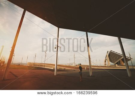 Wide angle shoot of modern contemporary asphalted area with for extreme sports recreation and parkour in Barcelona Forum with silhouette of curly girl huge solar station in distance