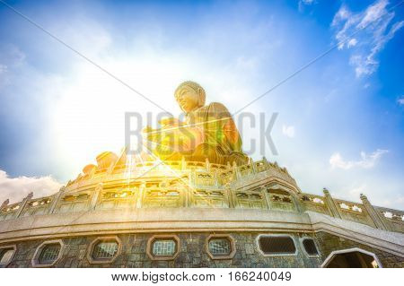 Scenic Tian Tan Buddha or Big Buddha, a large bronze statue at Ngong Ping, Lantau Island, Hong Kong, with sunbeams. Concept of spirituality and practice of meditating. Icon of pilgrimage in Asia.