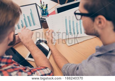 Close Up Of Two Young Managers Expertising Diagrama Of Financial Growth