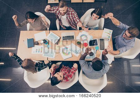 Top View Of Young Happy Multinational Colleagues Achived Financial Growth Of Company