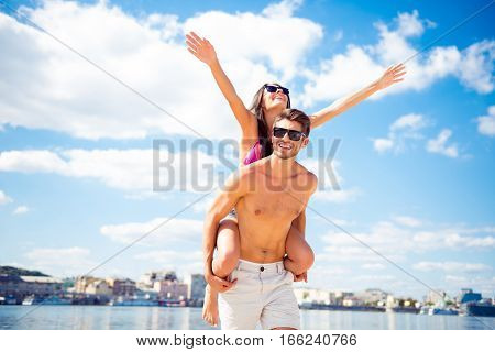 Travel And Honeymoon Lifestyle. Young Man Piggybacking His Wife Near The Sea