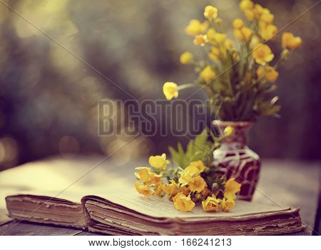 Bouquet of buttercups in a vase and the old open book on a wooden table.