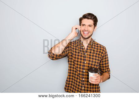 Portrait Of Happy Man Talking On Phone And Drinking Tea