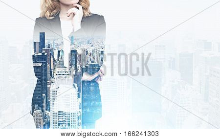 Close up of a red haired woman in a suit standing against a city panorama. Mock up. Toned image. Double exposure.