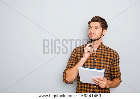 Portrait Of Minded Man With Notebook Isolated On Gray Background